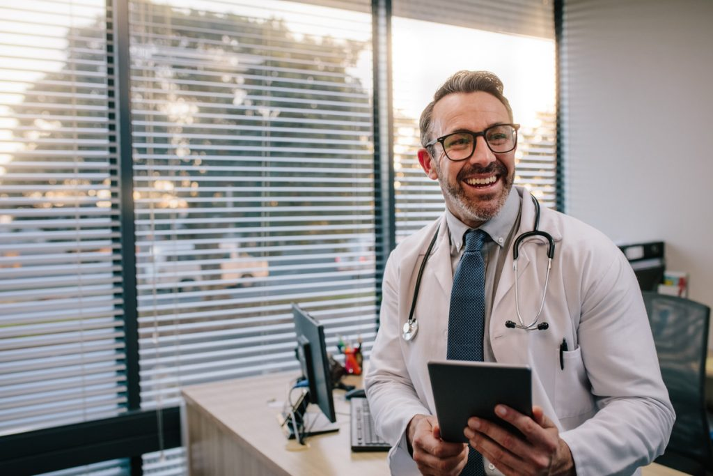 """Médico com tablet nas mãos no artigo """"Médico empreendedor"""""""